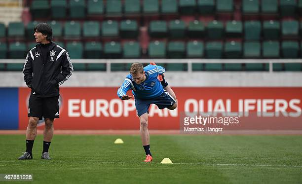 Head coach Joachim Loew of Germany observes the stretching session of Andre Schuerrle of Germany during a Germany training session ahead of their...