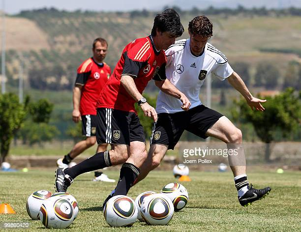Head coach Joachim Loew of Germany runs for the ball with Arne Friedrich during the German National Team training session at Verdura Golf and Spa...