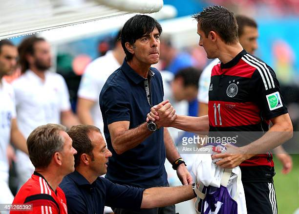 Head coach Joachim Loew of Germany shakes hands with Miroslav Klose of Germany at the begining of the second half during the 2014 FIFA World Cup...