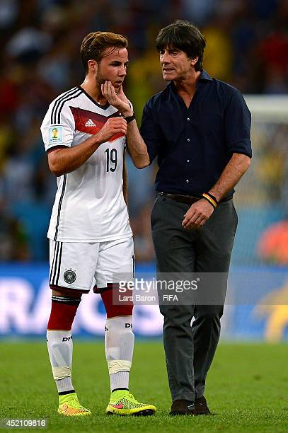 Head coach Joachim Loew of Germany speaks to Mario Goetze of Germany before the extra time during the 2014 FIFA World Cup Brazil Final match between...