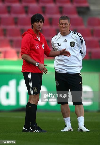 Head coach Joachim Loew speaks with Bastian Schweinsteiger during the Germany training session at RheinEnergieStadion on September 6, 2010 in...
