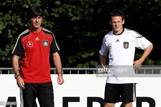 Head coach Joachim Loew stands next to Sascha Riether during the Germany training session at the Commerzbank Arena on August 9, 2010 in Frankfurt am...