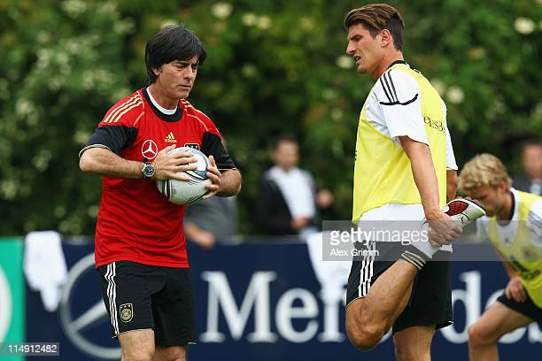 Head coach Joachim Loew walks past Mario Gomez during a training session of Germany at the Commerzbank Arena on May 28, 2011 in Frankfurt am Main,...