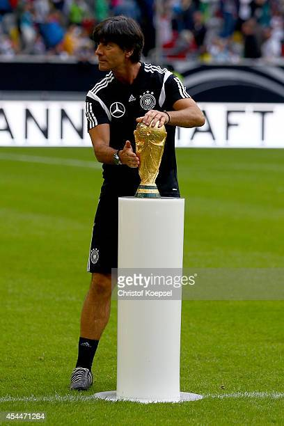 Head coach Joachim Loeww of Germany presents the World Cup trophy during a traning session at EspritArena on September 1 2014 in Duesseldorf Germany