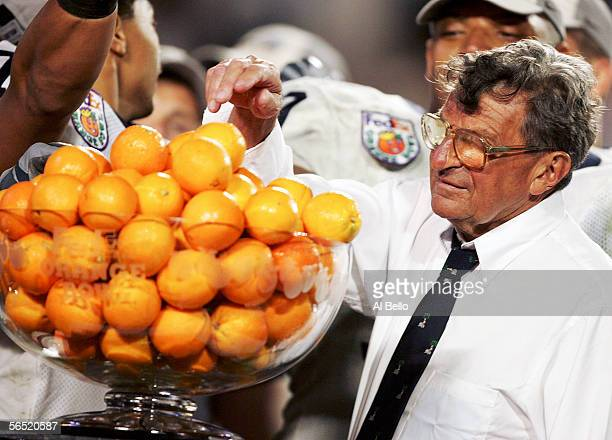 Head coach Joe Paterno of the Penn State Nittany Lions grabs an orange from the Orange Bowl Trophy after defeating the Florida State Seminoles in...