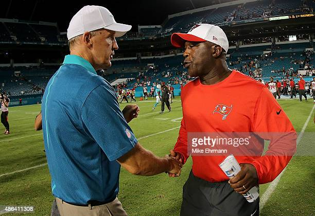 Head coach Joe Philbin of the Miami Dolphins and head coach Lovie Smith of the Tampa Bay Buccaneers chake hands during a preseason game at Sun Life...