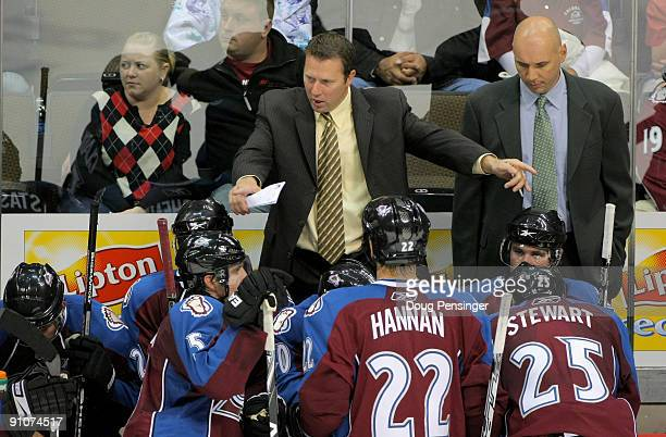 Head coach Joe Sacco of the Colorado Avalanche leads his team during a time out as assistant coach Sylvain Lefebvre looks on against the Los Angeles...