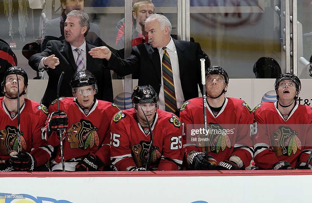 Head Coach Joel Quenneville discusses the game with assistant coach Mike Haviland behind the Chicago Blackhawks bench during the NHL game against the Columbus Blue Jackets on January 10, 2012 at the United Center in Chicago, Illinois.