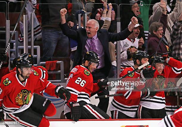 Head coach Joel Quenneville of the Chicago Blackhawks celebrates an overtime win against the St Louis Blues as members of his team jump from the...