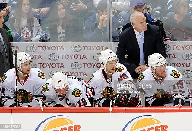 Head Coach Joel Quenneville of the Chicago Blackhawks looks on from the bench during second period action against the Winnipeg Jets on March 29 2015...