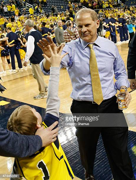 Head coach John Beilein high fives a young fan after beating the Michigan State Spartans 7970 at Crisler Center on February 23 2014 in Ann Arbor...