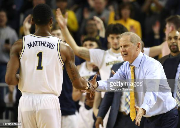 Head coach John Beilein of the Michigan Wolverines celebrates with Charles Matthews as he leaves the game while playing the Wisconsin Badgers at...