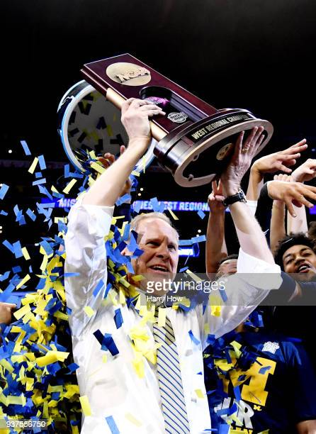 Head coach John Beilein of the Michigan Wolverines celebrates with the regional championship trophy after defeating the Florida State Seminoles in...