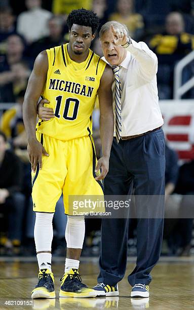 Head coach John Beilein of the Michigan Wolverines gives directions to Derrick Walton Jr #10 during overtime of a Big Ten game against the Wisconsin...