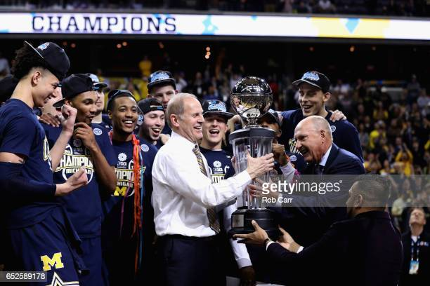Head coach John Beilein of the Michigan Wolverines grabs the trophy after winning the Big Ten Basketball Tournament Championship game against the...