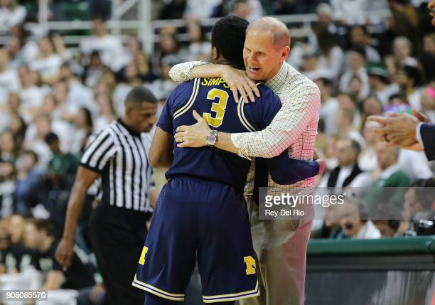 Head coach John Beilein of the Michigan Wolverines hugs Zavier Simpson of the Michigan Wolverines during a timeout against the Michigan State...