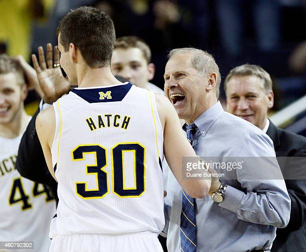 Head coach John Beilein of the Michigan Wolverines smiles at Austin Hatch as he leaves the game against the Coppin State University Eagles after...