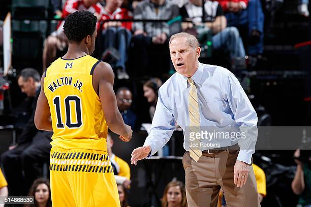 Head coach John Beilein of the Michigan Wolverines talks to Derrick Walton Jr #10 on the sideline against the Northwestern Wildcats in the second...