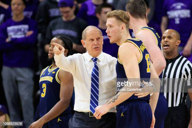 Head coach John Beilein of the Michigan Wolverines talks to Ignas Brazdeikis of the Northwestern Wildcats during a time out in the game against the...