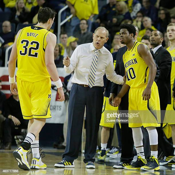Head coach John Beilein of the Michigan Wolverines talks with players Ricky Doyle and Derrick Walton Jr #10 during the second half of a Big Ten game...