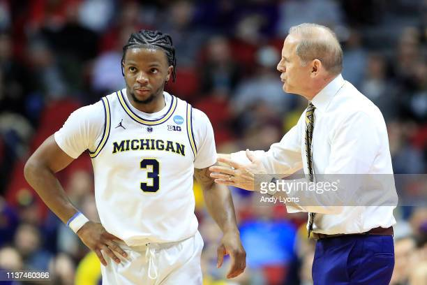 Head coach John Beilein speaks with Zavier Simpson of the Michigan Wolverines against the Montana Grizzlies in the first half during the first round...