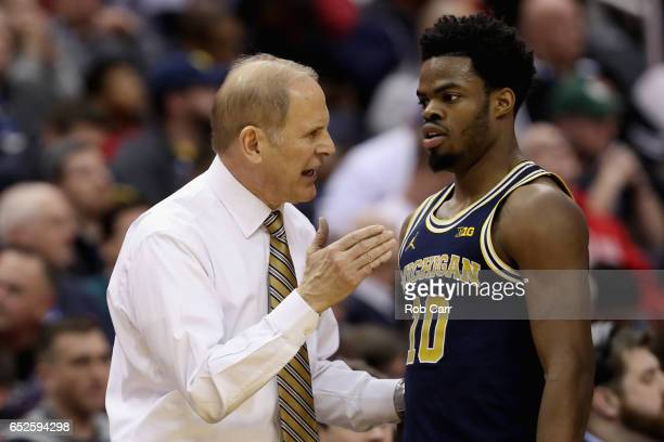 Head coach John Beilein talks with Derrick Walton Jr #10 of the Michigan Wolverines in the second half against the Wisconsin Badgers during the Big...