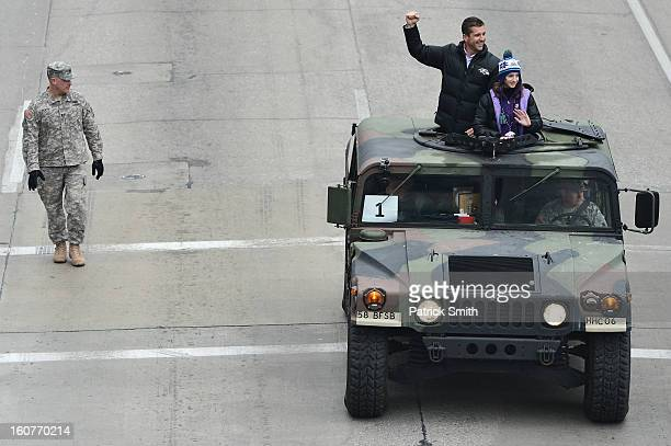 Head coach John Harbaugh of the Baltimore Ravens and his daughter Alison wave to fans as he and his players celebrate during their Super Bowl XLVII...