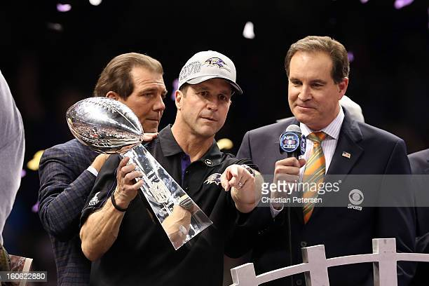 Head coach John Harbaugh of the Baltimore Ravens holds the VInce Lombardi trophy as CBS announcer Jim Nantz looks on after the Ravens won 3431...