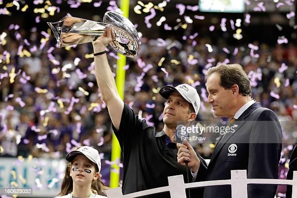 Head coach John Harbaugh of the Baltimore Ravens holds up the Vince Lombardi Trophy next to CBS host Jim Nantz following their 3431 win against the...