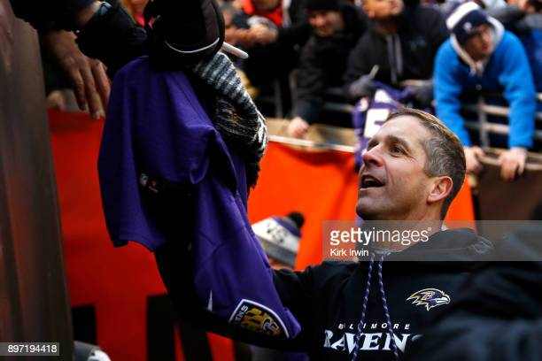 Head coach John Harbaugh of the Baltimore Ravens signs an autograph for a fan after the completion of the game against the Cleveland Browns at...