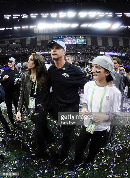 Head coach John Harbaugh of the Baltimore Ravens walks on the field with his wife Ingrid and daughter Alison as the Ravens celebrate their 3431 win...