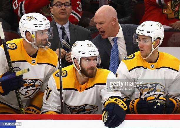 Head coach John Hynes of the Nashville Predators gives instructions to players on the bench during a game against the Chicago Blackhawks at the...
