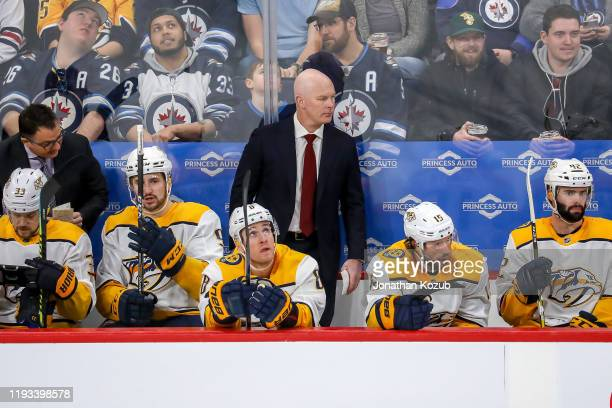 Head Coach John Hynes of the Nashville Predators looks on from the bench during first period action against the Winnipeg Jets at the Bell MTS Place...