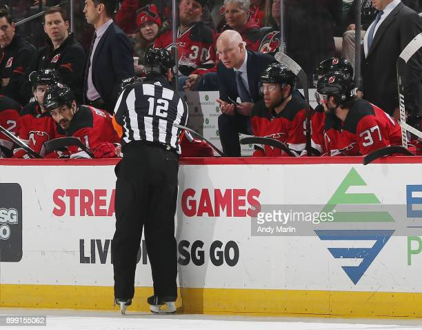 Head Coach John Hynes of the New Jersey Devils talks with referee Justin StPierre during his 200th NHL game as the Devils coach against the Detroit...
