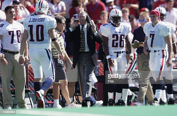 Head coach John Mackovic of Arizona directs his quarterback Jason Johnson in between plays against Wisconsin on September 21 2002 at Camp Randall...