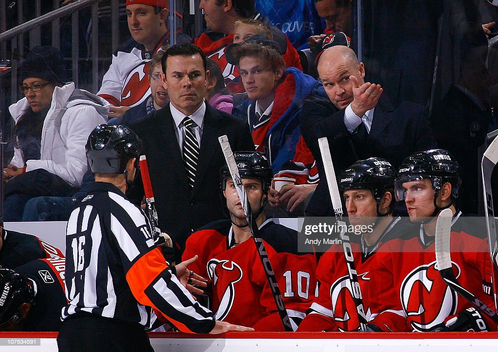 Head coach John MacLean (R) of the New Jersey Devils has a discussion with referee Brian Pochmara during the game against the Detroit Red Wings at the Prudential Center on December 11, 2010 in Newark, New Jersey.