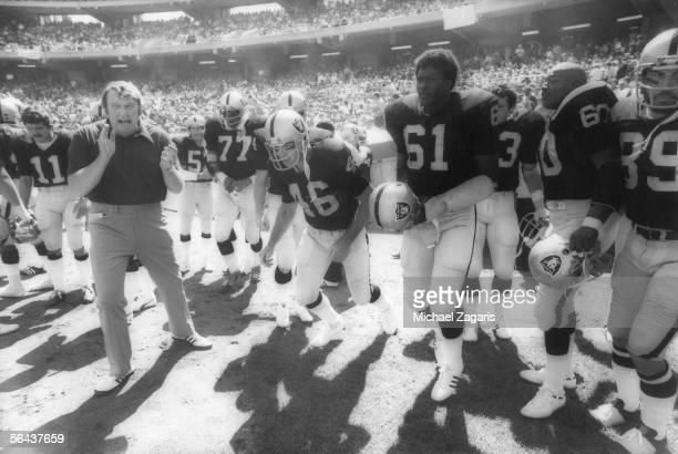 Head coach John Madden of the Oakland Raiders leads his team including running back Warren Bankston and defensive lineman Herb McMath onto the field...