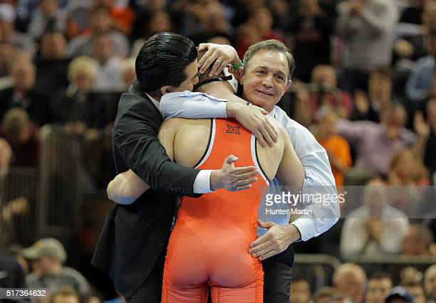 Head coach John Smith and assistant head coach Eric Guerrero of the Oklahoma State Cowboys celebrate after Dean Heil defeats Bryce Meredith of the...