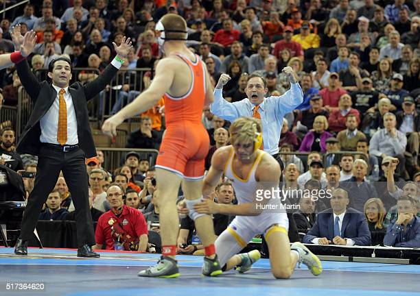 Head coach John Smith of the Oklahoma State Cowboys celebrates as Dean Heil wins his match over Bryce Meredith of the Wyoming Cowboys during the...