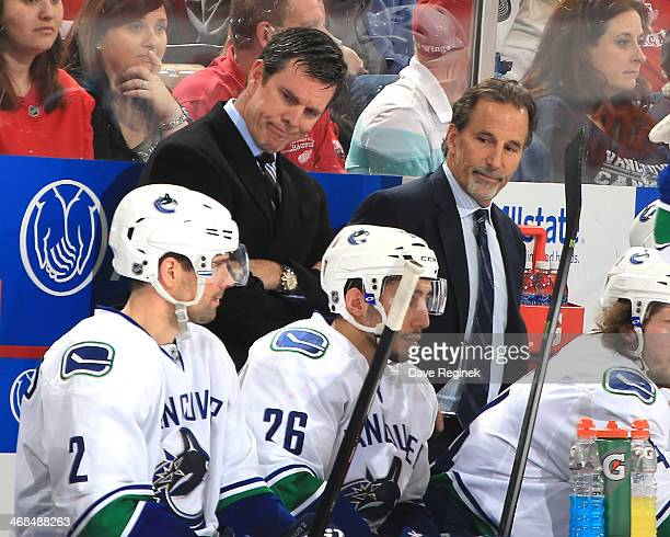 Head coach John Tortorella and Assistant coach Mike Sullivan of the Vancouver Canucks look down at players Dan Hamhuis and Frank Corrado of the...