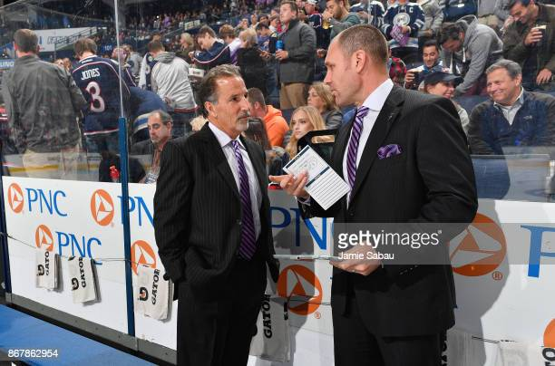 Head Coach John Tortorella of the Columbus Blue Jackets and Assistant Coach Brad Larsen of the Columbus Blue Jackets talk on the bench before a game...