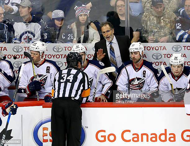 Head Coach John Tortorella of the Columbus Blue Jackets holds a discussion with referee Brad Meier during a second period stoppage in play against...