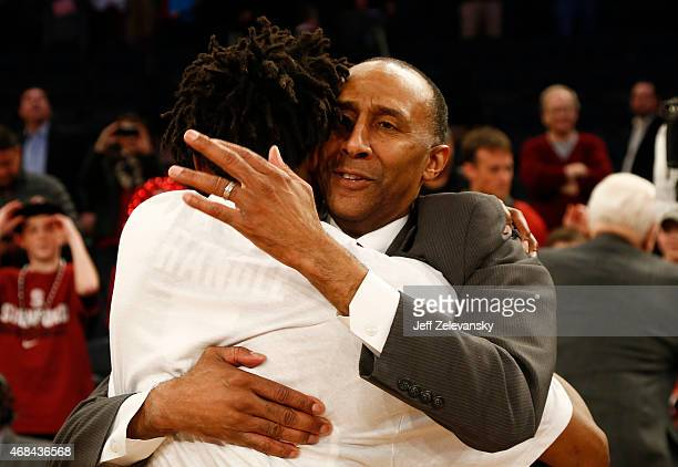 Head coach Johnny Dawkins oembraces Chasson Randle of the Stanford Cardinal after victory over Miami Hurricanes during the NIT Championship at...