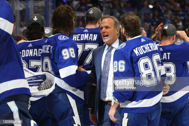 Head coach Jon Cooper of the Tampa Bay Lightning celebrates with Mikhail Sergachev and Nikita Kucherov after defeating the New York Islanders 1-0 in...