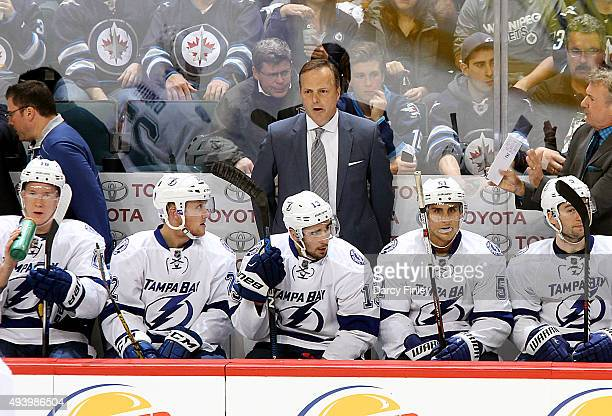 Head Coach Jon Cooper of the Tampa Bay Lightning looks on from the bench during second period action against the Winnipeg Jets at the MTS Centre on...
