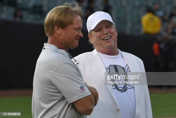 Head coach Jon Gruden and Owner Mark Davis of the Oakland Raiders talking with each other while looking on as their team warms up prior to the start...