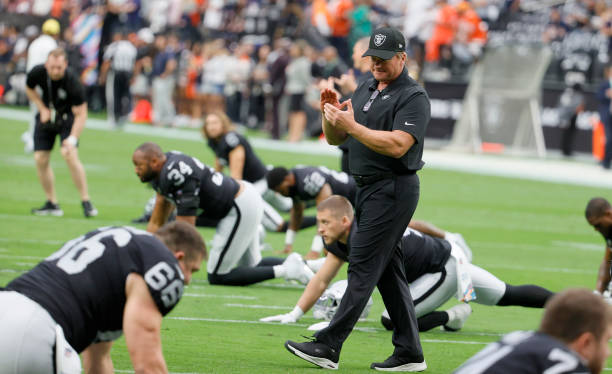 Head coach Jon Gruden of the Las Vegas Raiders talks to his players as they stretch before a game against the Chicago Bears at Allegiant Stadium on...