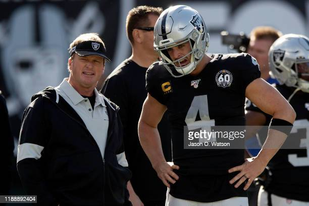 Head coach Jon Gruden of the Oakland Raiders talks to quarterback Derek Carr before the game against the Jacksonville Jaguars at RingCentral Coliseum...
