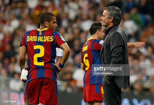 Head coach Jose Guardiola of Real Madrid smiles beside Daniel Alves of Barcelona during the La Liga match between Real Madrid and Barcelona at...