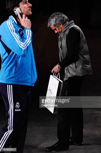 Head Coach Jose Mourinho checks his mobile phone as his assitant Aitor Karanka of Real Madrid CF talks on his mobile phone at the end of the Copa del...
